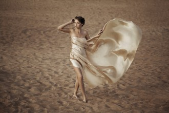 Picture of woman in flying gold cloth in the sand