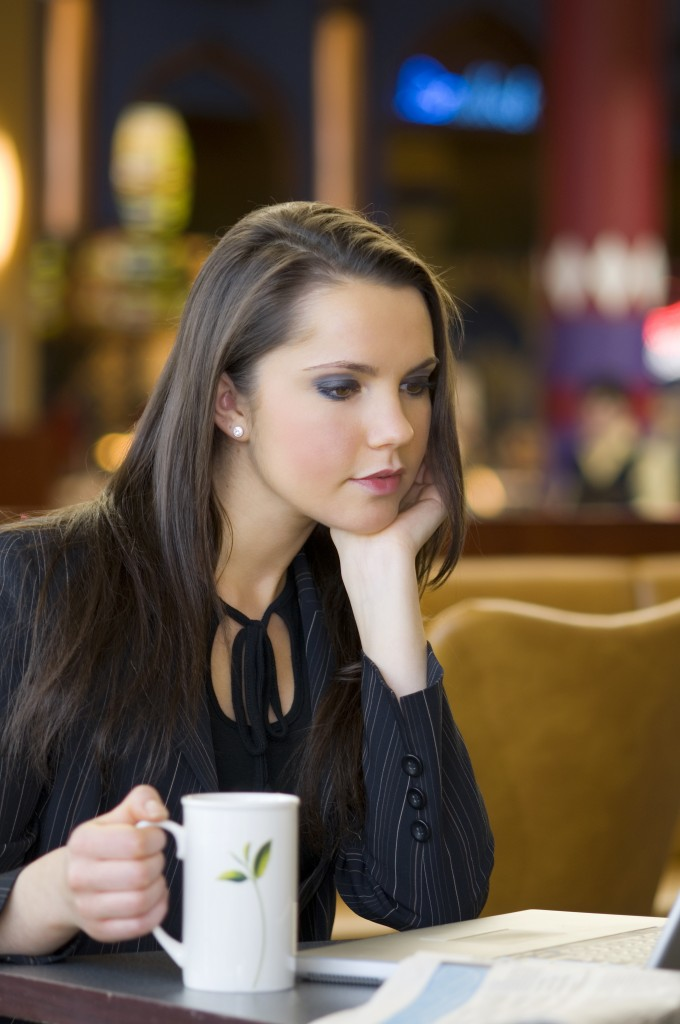 young business woman taking a cup of tea sitting in a bar